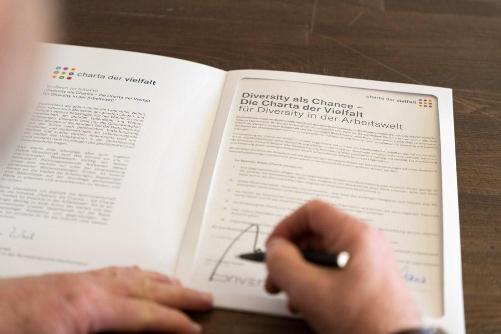 Stefan hencke setzt seine Untecrschrift auf die Charta der Vielfalt.