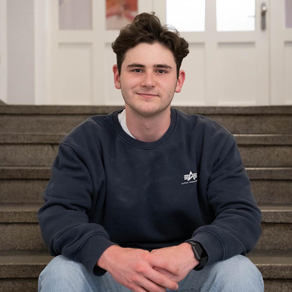 Das Bild zeigt Praktikant Erik Goldschmid vor dem Convensis-Büro sitzend.